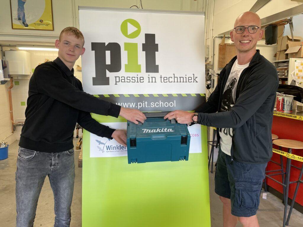 docent Rick overhandigt leerling Raymond de boormachine van Makita